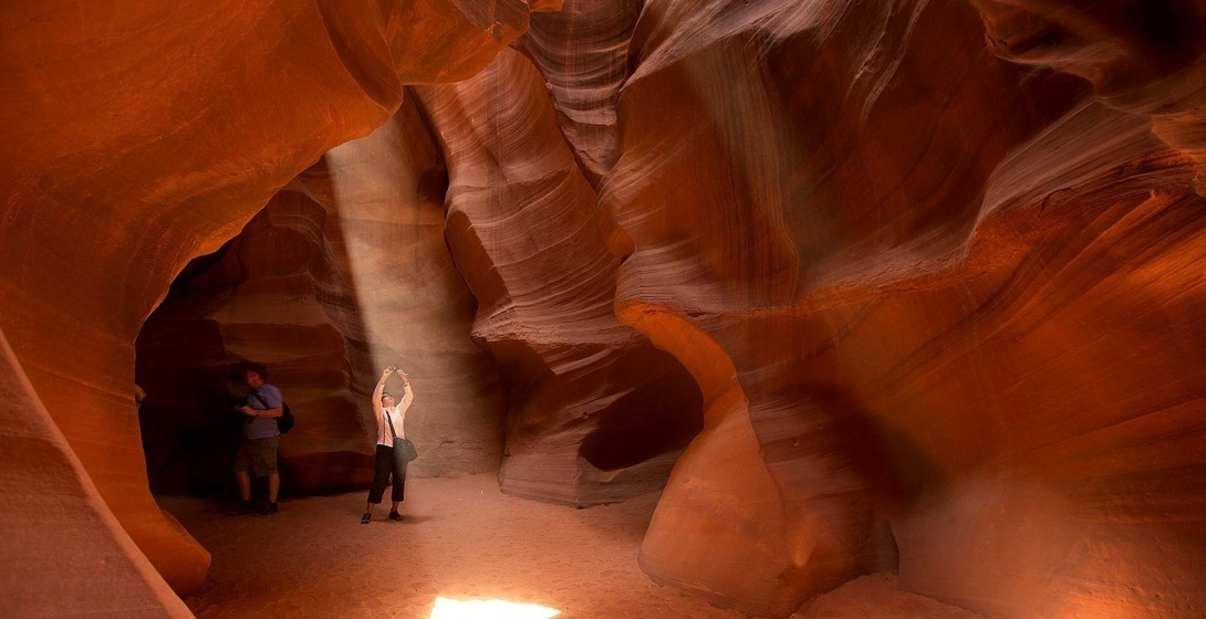 MAY 21: Tourists stop to photograph shafts of light coming through the sandstone canyon walls while touring through Antelope Canyon, near Page, Arizona. (Julie Jacobson/Associated Press)